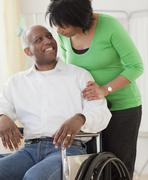 African woman pushing husband in wheelchair Stock Photos