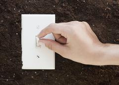 Woman flipping light switch in soil Stock Photos