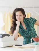 Mixed race woman leaning on cash register Stock Photos