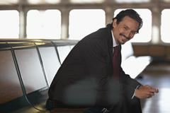 Stock Photo of smiling mixed race businessman on bench