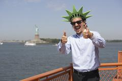 mixed race businessman on ferry wearing statue of liberty hat - stock photo