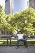 Mixed race man smiling on park bench Stock Photos