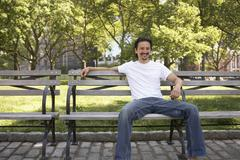 mixed race man smiling on park bench - stock photo