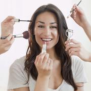 hands applying makeup to hispanic woman's face hands applying makeup to hispanic - stock photo