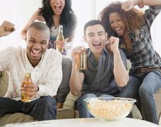Friends drinking beer and watching football on television Stock Photos