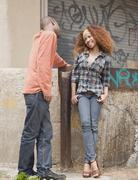 Man and woman flirting on urban street Stock Photos