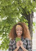 Mixed race woman holding leaf under tree Stock Photos