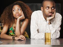 Couple sitting at bar and looking irritated Stock Photos