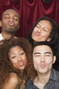 friends puckering lips in photo booth - stock photo