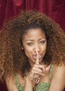 mixed race woman gesturing quiet - stock photo
