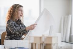 Stock Photo of hispanic woman looking at blueprints