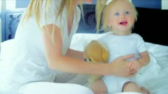Blonde Mom Bouncing Young Child Bedroom Stock Footage
