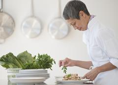 chinese chef plating meals in professional kitchen - stock photo