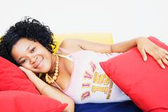 african woman laying on sofa - stock photo