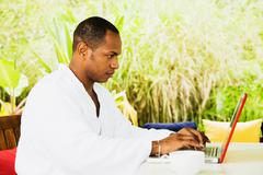 Stock Photo of mixed race man using laptop in bathrobe on patio