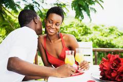 African couple drinking orange juice on patio Stock Photos