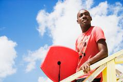 African man holding body board Stock Photos