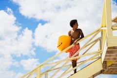 african man holding body board on lifeguard hut ramp - stock photo