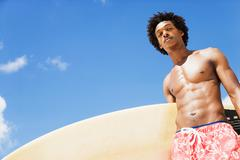 Serious african man holding surfboard Stock Photos