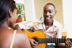 African man playing guitar for woman Stock Photos