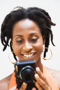 African woman holding digital camera Stock Photos