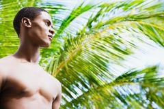 Bare chested african man in front of palm tree looking pensive Stock Photos