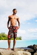 African man in swim trunks standing on rocks by ocean Stock Photos