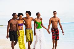 African friends walking on beach Stock Photos
