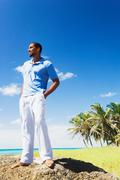 African man standing on rock near ocean Stock Photos