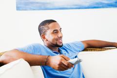 Afrikkalainen mies katselee televisiota Kuvituskuvat