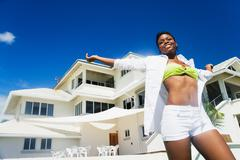 African woman with arms outstretched poolside Stock Photos