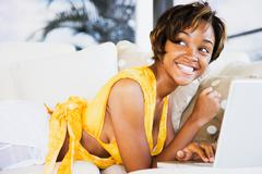 African woman using laptop on sofa Stock Photos