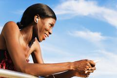 African woman wearing headphones and holding mp3 player Stock Photos