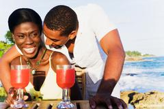 African couple drinking cocktails on patio overlooking ocean Stock Photos