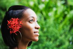 African woman with flowers in hair looking up Stock Photos