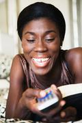 African woman holding remote control Stock Photos