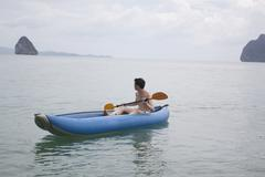 Chinese man paddling boat in ocean Stock Photos