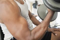 african man doing biceps curls with dumbbell - stock photo