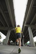 mixed race man running under freeway overpass - stock photo