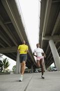 couple running under freeway overpass - stock photo