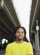 Mixed race man smiling under freeway overpass Stock Photos