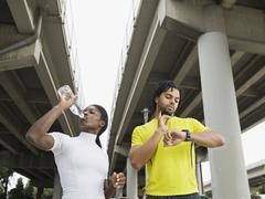 Runners taking a break under freeway overpass Stock Photos