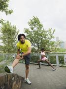 couple stretching on sidewalk - stock photo