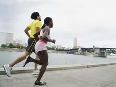 couple running along urban waterfront - stock photo