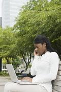 African businesswoman using laptop on bench in city Stock Photos