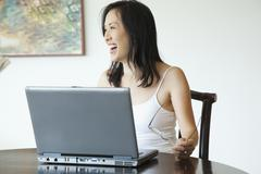 japanese woman using laptop at table - stock photo