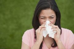 Hispanic woman blowing nose Stock Photos