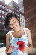 Mixed race woman picking petals off flower on urban street Stock Photos