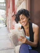 Mixed race woman reading classified ads on urban street Stock Photos