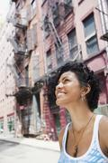 Mixed race woman looking up on urban street Stock Photos